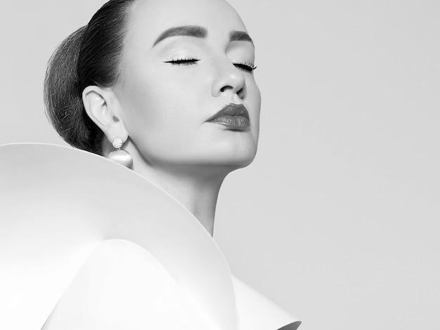 白いドレスを着た美しいエレガントな女性の黒と白のアートスタジオの肖像画。