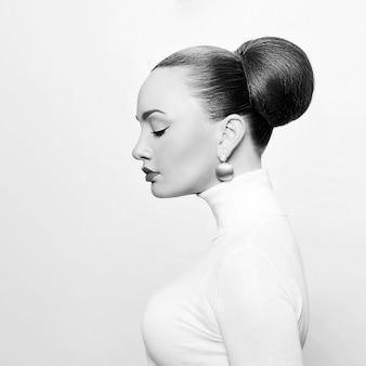 白いタートルネックの美しいエレガントな女性の黒と白のアートスタジオの肖像画。