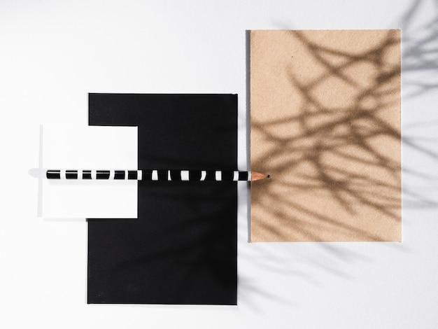 스트라이프 연필이 달린 검은 색과 흰색 담요와 가지 그림자가있는 베이지 색 담요