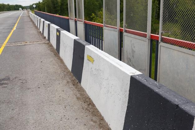 Черно-белая граница. барьер, предназначенный для предотвращения съезда автомобиля с моста