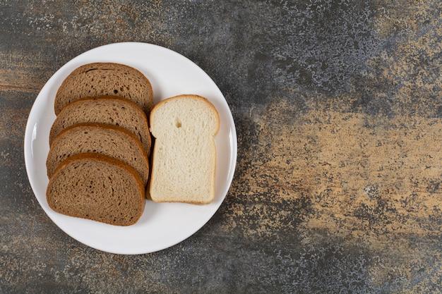白いプレート上の黒と白のパンのスライス