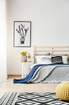 노란색 신선한 꽃, 더블 침대, 무늬가 있는 카펫이 있는 밝은 침실 내부의 벽에 걸린 흑백 선인장 포스터