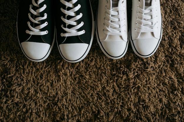 茶色のカーペットに黒と白のキャンバスシューズ
