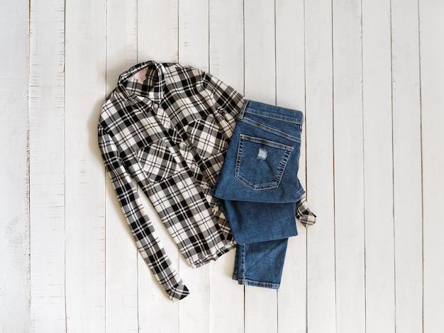 黒と白の市松模様のシャツと木製の背景にジーンズ。上面図
