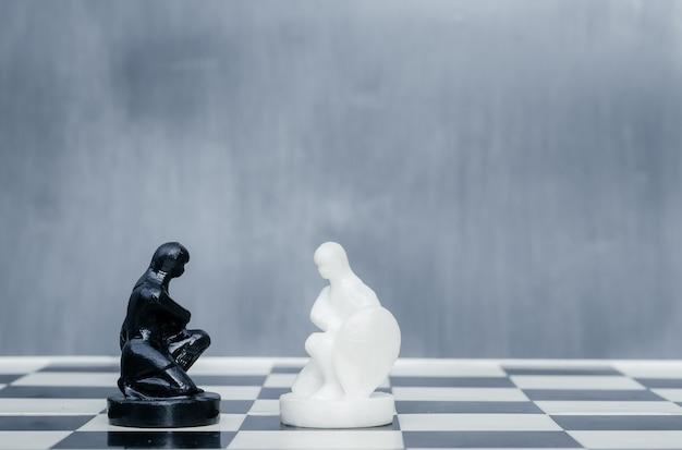 Черно-белые шахматные фигуры на шахматной доске. концепция борьбы с расизмом. мотивационный плакат против расизма и дискриминации.