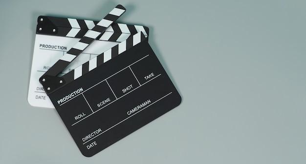 灰色の背景に黒と白のカチンコまたはカチンコまたは映画のスレート。