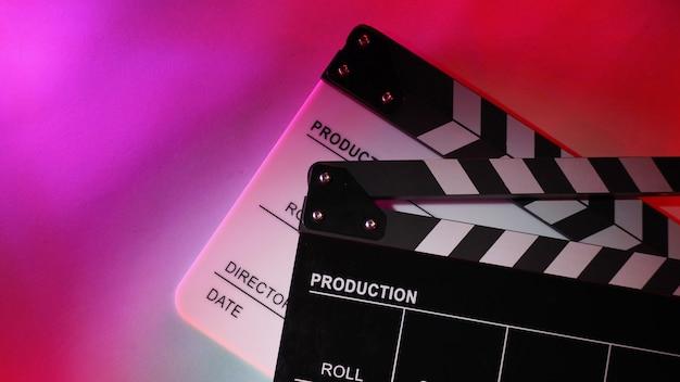 흑백 클래퍼보드 또는 영화 클래퍼 보드 또는 빨간색, 보라색, 민트 녹색 또는 다중 색상 배경의 슬레이트.