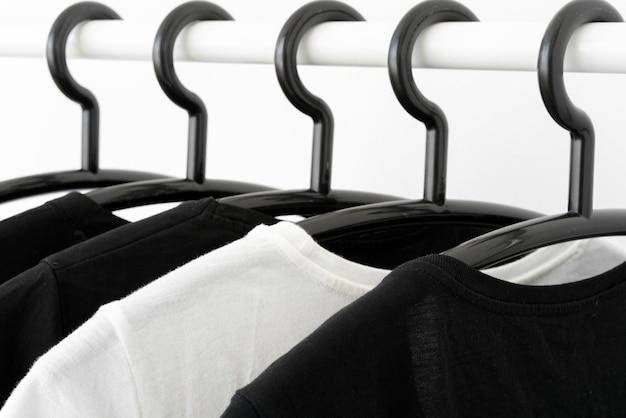 ワードローブのハンガーに黒と白の色調の服。女性のミニマリストのワードローブ。水平バナー