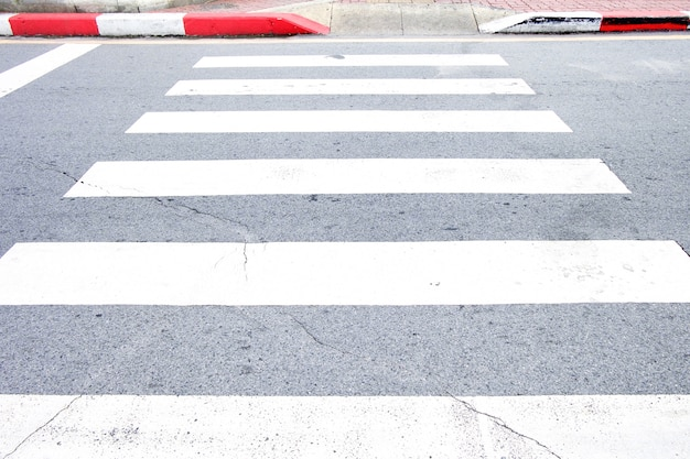 黒と白の横断歩道と白と赤の歩道の端。