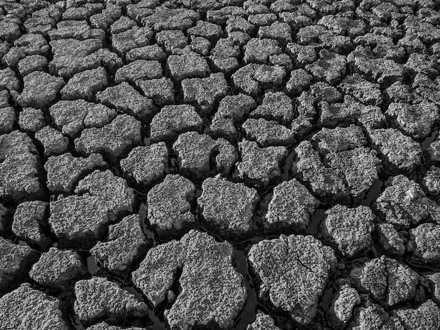 Черно-белые сушеные потрескавшиеся дно озера фоновой текстуры глобального потепления