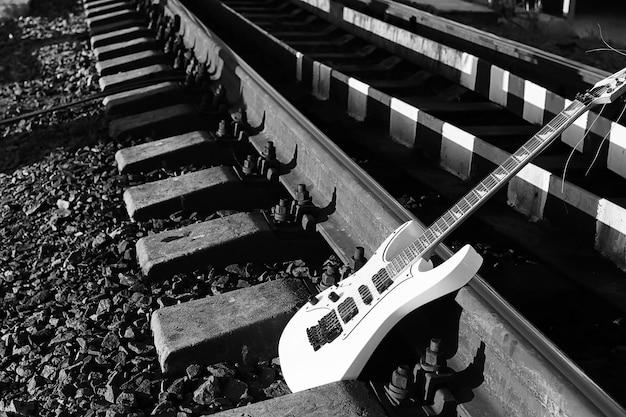線路と工業用灰色の石の黒と白のエレキギター