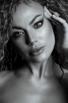 ウェーブのかかった髪と裸の肩を持つ情熱的な女性の黒と白のファッションの肖像画