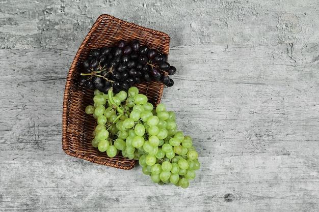 木製のバスケットに黒と白の新鮮なブドウ。