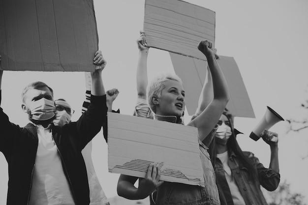 검정색과 흰색. 집회에서 구호를 외치는 활동가 그룹. 백인 남성과 여성이 도시에서 함께 행진하고 있다. 화난 표정, 희망적이고 자신감 있는 표정. 디자인 또는 광고를 위한 빈 배너입니다.