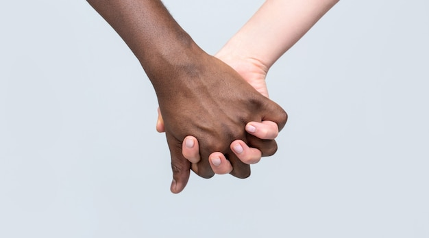 흑인과 백인 손 사랑 파트너십입니다. 흑인, 백인 여자와 남자가 함께 손을 잡고 있습니다. 백인 여자, 아프리카 남자 손 우정 기호를 들고. 아프리카 평화의 상징. 손을 잡고 혼혈 부부