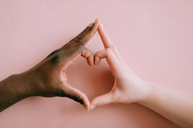 ハート形の黒と白の手。異人種間の友情の概念。