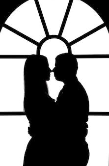 ステンドグラスの窓の背景に抱き締める男と女の姿の白黒イラスト