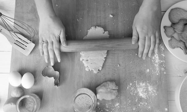 休日のクッキーのために生地を準備している女性の上からの黒と白の画像
