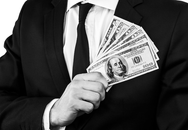 一定量の米ドル紙幣を持っている黒いスーツを着た若い男の白黒画像