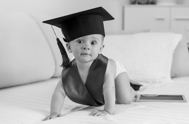 Черно-белое изображение очаровательного 10-месячного мальчика в выпускной шапке, ползающего по кровати