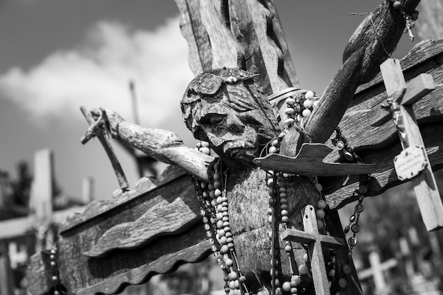 リトアニア、シャウレイの十字架の丘にあるキリストの古い木製の十字架の白黒画像。十字架の丘は、歴史と宗教的な民芸品のユニークな記念碑です。