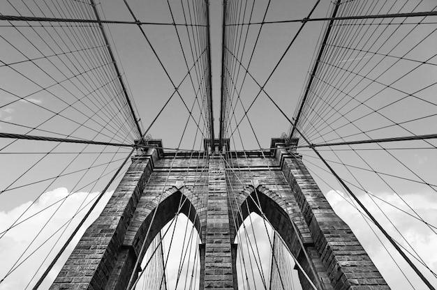 Черно-белое изображение бруклинского моста в нью-йорке против неба с облаками
