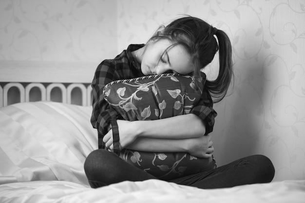 Черно-белое изображение депрессивной девочки-подростка, сидящей на кровати и обнимающей подушку