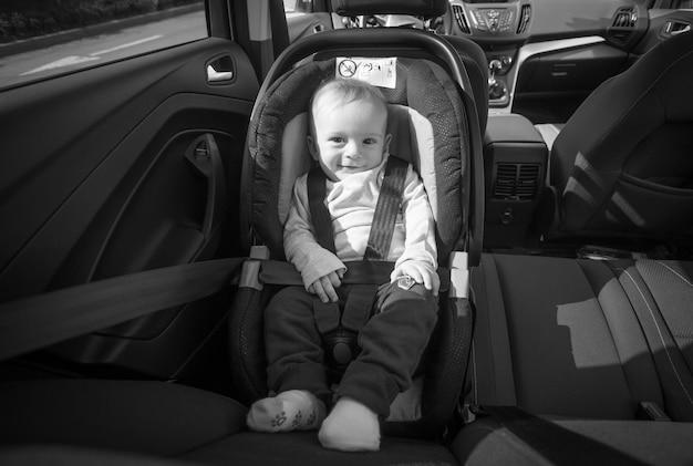 Черно-белое изображение счастливого улыбающегося мальчика, позирующего в детском автокресле