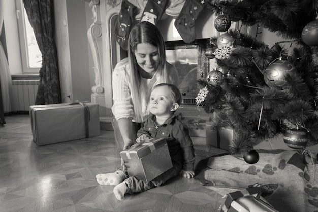 거실 바닥에 크리스마스 선물을 들고 있는 엄마와 아기의 흑백 이미지