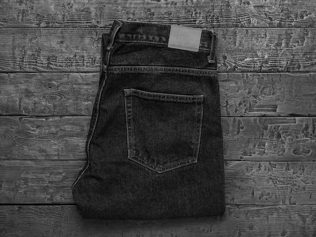 Черно-белое изображение стильных мужских джинсов на деревянном столе. классическая джинсовая одежда. плоская планировка. вид сверху.