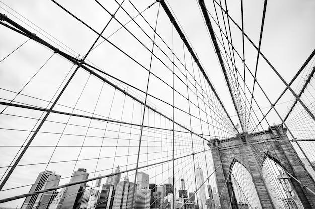 Черно-белое изображение бруклинского моста в нью-йорке. манхэттен на фоне линии горизонта