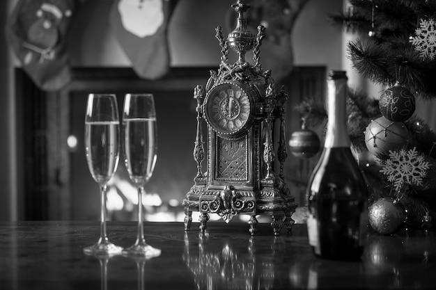 오래된 시계 옆 탁자에 있는 샴페인 두 잔의 흑백 이미지는 12시 방향을 보여줍니다. 흑백 크리스마스 배경