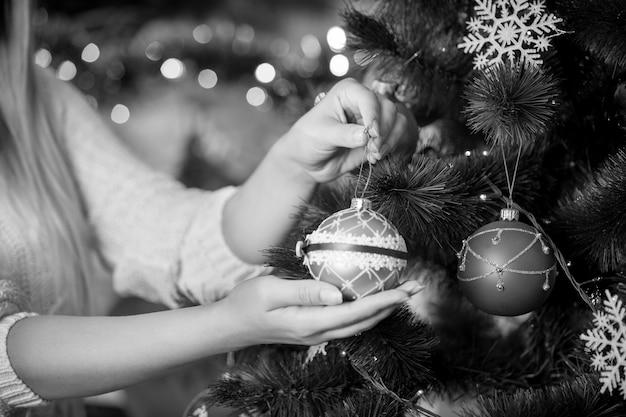 クリスマスツリーを飾る女性の白黒画像