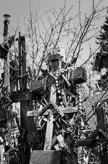 リトアニア、シャウレイの十字架の丘にある木製の十字架と十字架の白黒画像。十字架の丘は、歴史と宗教的な民芸品のユニークな記念碑です。