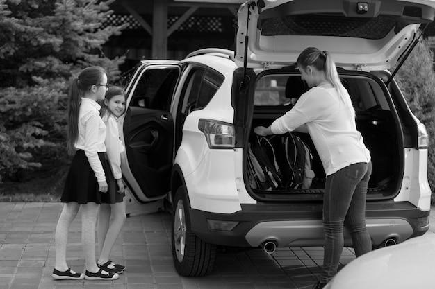 Черно-белое изображение молодой матери и двух дочерей, садящихся в машину, чтобы пойти в школу