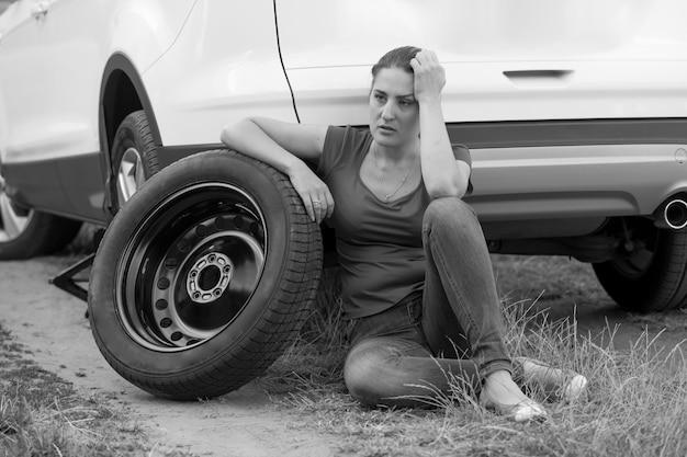 깨진 차에 바닥에 앉아 젊은 화가 여자의 흑백 이미지