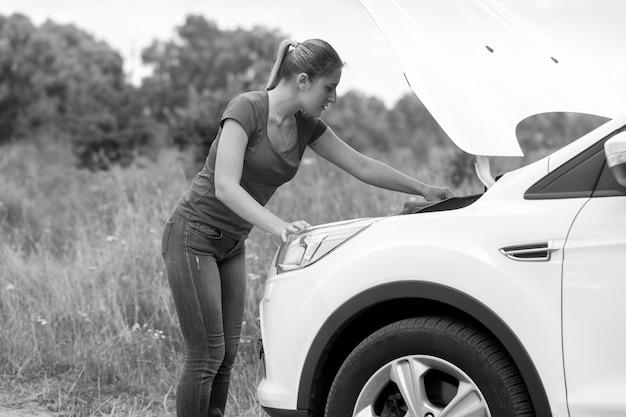 牧草地で過熱した車のボンネットの下を見て若い女性の白黒画像