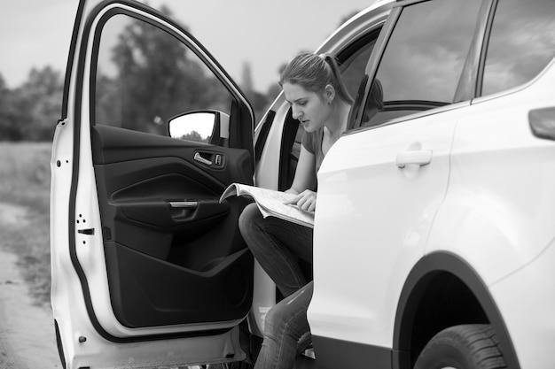 地図上で道路を探して車に座っている若い女性の白黒画像