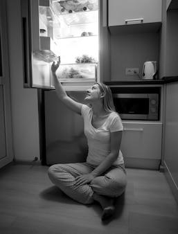 Черно-белое изображение молодой женщины, сидящей на полу и тянущейся к еде из открытого холодильника поздно ночью