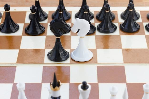 黒のチェスの前にいる黒と白の騎士