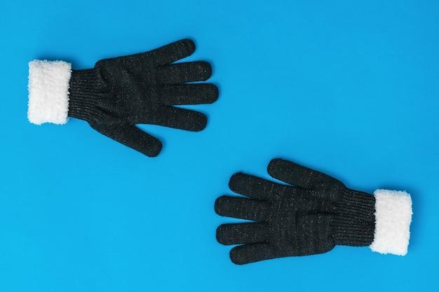 黒と白のニット手袋は、青い背景でお互いに手を伸ばします。希望と出会いのコンセプト。ファッションレディースアクセサリー。