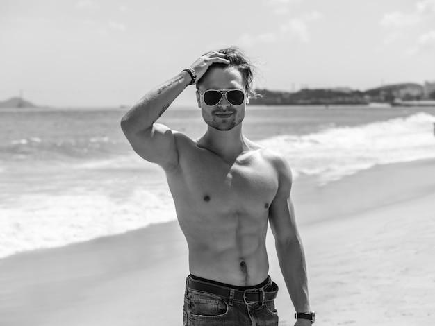 Черно-белый мускулистый мужчина на пляже