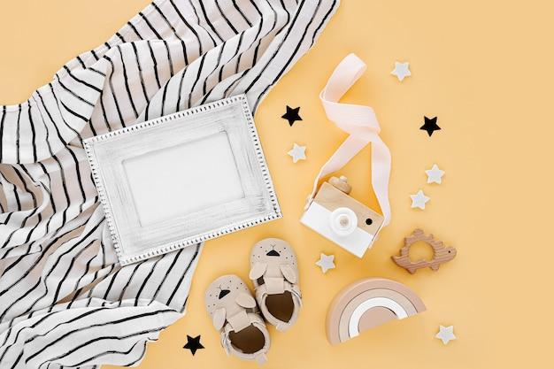 Черно-белое пеленальное одеяло из муслина с фоторамкой и детские тапочки, игрушки на желтом фоне. набор гендерно-нейтральных аксессуаров для новорожденных. плоская планировка, вид сверху