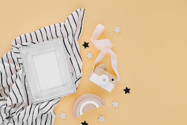 Черно-белое пеленальное одеяло из муслина с фоторамкой и детскими игрушками на желтом фоне. набор гендерно-нейтральных аксессуаров для новорожденных. плоская планировка, вид сверху
