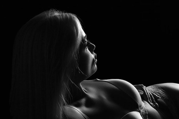 美しい女性のシルエットの白黒写真、暗い写真。横をよく見る