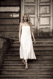 Черно-белое фото красивой молодой женщины в белом платье, спускающейся по лестнице на фоне старинного здания с дверьми. концепция готического романа