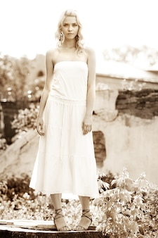 오래 된 건물의 배경에 서 있는 흰 드레스에 아름 다운 젊은 여자의 흑백 사진. 고딕 로맨스 개념