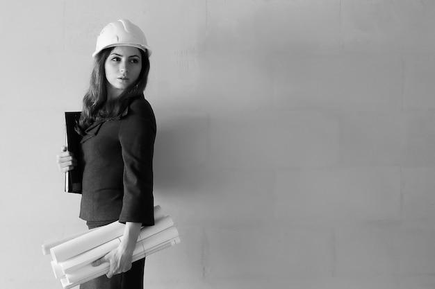 図面とノートと建設現場での女性建築家の白黒写真