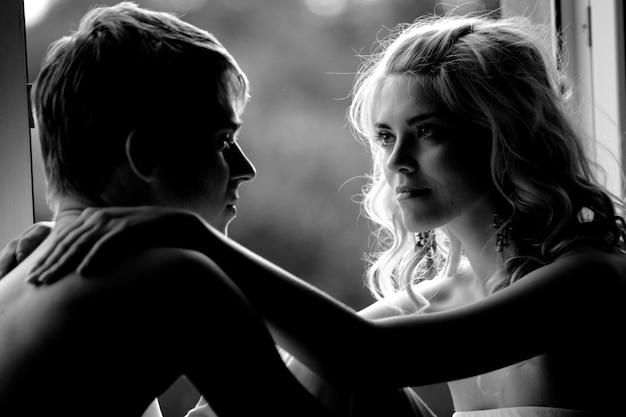 遠くを抱き締めてロマンチックに見ている恋をしている若いカップルの白黒写真。愛と恋愛と愛情に関する概念