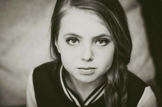Черно-белое фото молодой девушки-подростка, смотрящей прямо в камеру.